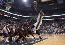 Al Jefferson des Jazz tente d'inscrire un panier face au Miami Heat. La surprise de la soirée de lundi est venue de l'Utah où les Jazz ont triomphé du Miami Heat, le champion en titre, malgré 32 points de LeBron James. /Photo prise le 14 janvier 2013/REUTERS/Jim Urquhart