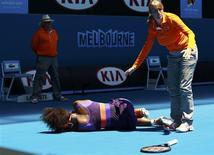 Avant de se qualifier pour le deuxième tour de l'Open d'Australie en écrasant la modeste Roumaine Edina Gallovits-Hall 6-0 6-0, Serena Williams a glissé sur le court de l'Hisense Arena, où elle s'est tordu la cheville et est restée allongée en attendant la venue du médecin. /Photo prise le 15 janvier 2013/REUTERS/Daniel Munoz