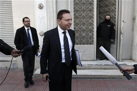 Greece's Finance Minister Yannis Stournaras (C) listens to a reporter's question outside State's General Accounting Office in Athens December 20, 2012. REUTERS/Yorgos Karahalis