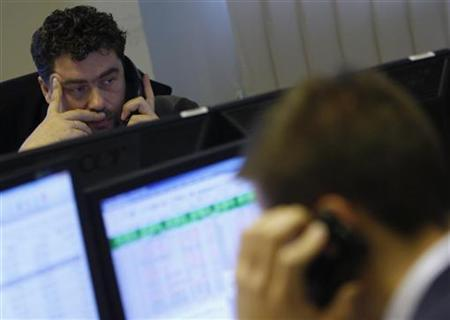 A Hungarian currency trader makes a phone call at his desk in the dealing room of a brokerage in Budapest November 25, 2011. REUTERS/Bernadett Szabo/Files