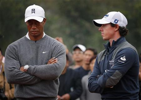 Tiger Woods (L) of the U.S. reacts as he stands next to fellow golfer Rory McIlroy of Northern Ireland during the trophy presentation after their exhibition event at the Jinsha Lake Golf Club in Zhengzhou, Henan Province October 29, 2012. REUTERS/David Gray