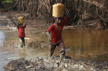 A man and his son walk through polluted farmland in the Kalaba community in Nigeria's oil state of Bayelsa November 26, 2012. REUTERS/Akintunde Akinleye