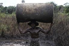 Ebiowei, 48, carries an empty oil container on his head to a place where it would be filled with refined fuel at an illegal refinery site near river Nun in Nigeria's oil state of Bayelsa November 27, 2012. Locals in the industry say workers can earn $50 to $60 a day. REUTERS/Akintunde Akinleye