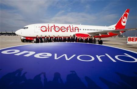 Chief Executive Officers of member airlines of the Oneworld alliance pose in front of a passenger plane during a ceremony marking Airberlin's accession to the network at the BBI airport outside Berlin, March 20, 2012. REUTERS/Thomas Peter (GERMANY - Tags: BUSINESS TRANSPORT)