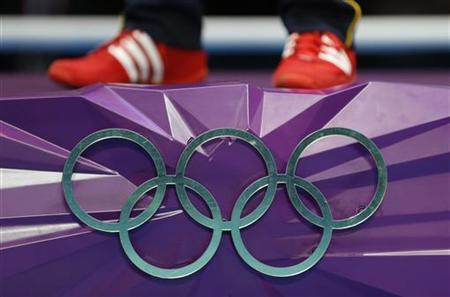 Gold medallist Vasyl Lomachenko of Ukraine stands atop the podium near the Olympic rings during the presentation ceremony for the Men's Light (60kg) boxing at the London Olympics August 12, 2012. REUTERS/Murad Sezer/Files