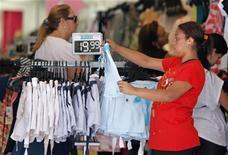Vendedora mostra roupas em loja no Rio de Janeiro, em novembro de 2012. As vendas no comércio varejista brasileiro perderam fôlego em novembro, ao avançarem 0,3 por cento ante outubro. 30/11/2012 REUTERS/Sergio Moraes