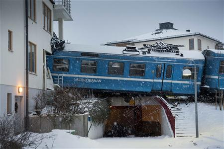 A local train that derailed and crashed into a residential building in Saltsjobaden is seen outside Stockholm in this picture taken by Scanpix Sweden January 15, 2013. According to local media, a spokesman from Arriva, the company that operates the train line, says the train was stolen by a domestic cleaner, who stole the train for unknown reasons. The cleaner was taken to a hospital after the crash. No residents in the building were injured. REUTERS/Jonas Ekstromer/Scanpix Sweden