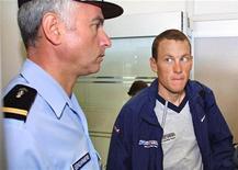 Lance Armstrong tendrá que testificar ante la comisión que investiga las acusaciones hechas contra la Unión Ciclista Internacional (UCI) si son ciertas las informaciones difundidas el martes sobre su confesión de dopaje. En la imagen, Lance Armstrong (D), entonces líder del equipo US Postal Service, mira a un gendarme francés antes de subir a un avión que lleva a los ciclista de Grenoble a Perpignan en una etapa de transición del Tour de Francia en esta foto de archivo del 19 de julio de 2001. REUTERS/Pool/Files