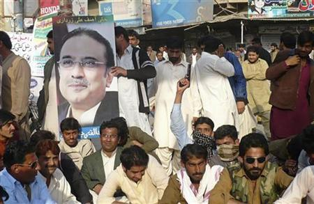 A supporter of Pakistan People's Party (PPP) holds a gun near a poster of Pakistan's President Asif Zardari during a protest against a Supreme Court decision to arrest Prime Minister Raja Pervez Ashraf in Larkana January 15, 2013. REUTERS/Stringer