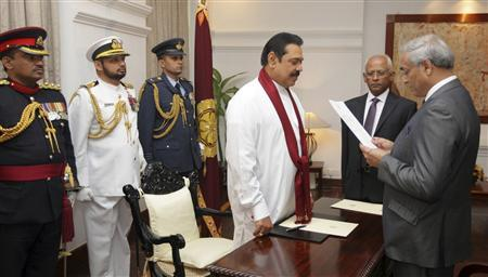 Sri Lanka's President Mahinda Rajapaksa looks on as the newly appointed Chief Justice Mohan Peiris (R) swears in, in Colombo in this picture provided by the Sri Lanka Presidential Media Office January 15, 2013. REUTERS/Presidential Media Office/Handout