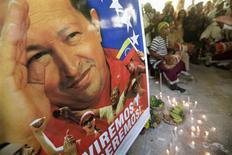 """Hugo Chávez recibió en Cuba a parte de su gabinete, dijo el martes el vicepresidente venezolano, Nicolás Maduro, señalando que el líder socialista """"va remontando la cuesta"""" tras sufrir varias complicaciones en una delicada operación realizada en diciembre para combatir el cáncer que padece. En esta imagen de archivo, un cartel con el rostro del presidente venezolano, Hugo Chávez, en una ceremonia de santería para pedir su recuperación en La Habana, el 10 de enero de 2013. REUTERS/Enrique De La Osa"""