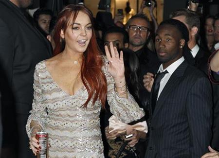 Actress Lindsay Lohan waves as she arrives for the Mr. Pink Ginseng Drink launch party at the Beverly Wilshire Hotel in Beverly Hills, California, October 11, 2012. REUTERS/Jonathan Alcorn/Files