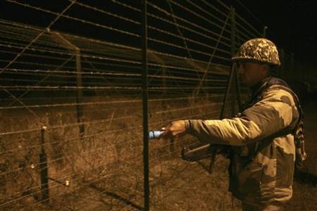 An Indian Border Security Force (BSF) soldier keeps vigil during night patrol near the fenced border with Pakistan in Abdullian, southwest of Jammu January 14, 2013. REUTERS/Mukesh Gupta