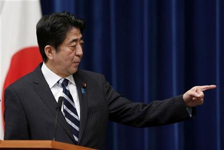Japan's Prime Minister Shinzo Abe points to a placard showing the government's emergency economic stimulus plan during a news conference at his official residence in Tokyo January 11, 2013. REUTERS/Issei Kato