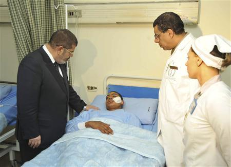 Egyptian President Mohamed Mursi talks with a soldier injured in a train accident at a hospital in Cairo January 15, 2013. REUTERS/Egyptian Presidency/Handout