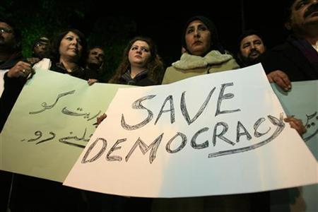 Members of the civil society hold placards during a protest against the Supreme Court decision to arrest Prime Minister Raja Pervez Ashraf in Lahore January 15, 2013. REUTERS/Mani Rana