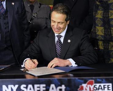 New York Governor Andrew Cuomo signs the New York Secure Ammunition and Firearms Enforcement Act at the Capitol in Albany, New York January 15, 2013. The bill was passed by both the Senate and Assembly during a news conference. REUTERS/Hans Pennink (UNITED STATES - Tags: SOCIETY POLITICS)