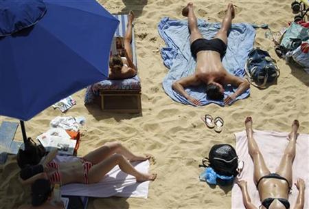 People sunbathe at ''Paris Plage'' (Paris Beach) in Paris, August 19, 2012. REUTERS/Vincent Kessler/Files