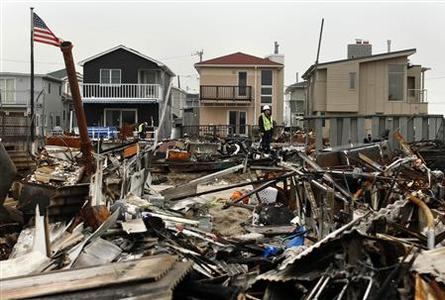 A man stands on the debris of homes devastated by fire and the effects of Hurricane Sandy in the Breezy Point section of the Queens borough in New York January 15, 2013. REUTERS/Shannon Stapleton (UNITED STATES - Tags: ENVIRONMENT DISASTER POLITICS)