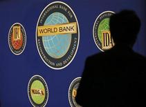 A man is silhouetted against the logo of the World Bank at the main venue for the International Monetary Fund (IMF) and World Bank annual meeting in Tokyo October 10, 2012. REUTERS/Kim Kyung-Hoon
