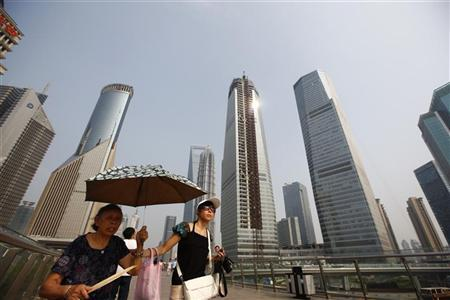 Visitors walk through the Lujiazui Financial Area in Shanghai, August 4, 2010. REUTERS/Aly Song
