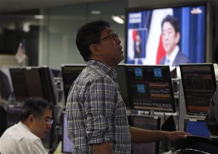 An employee of a foreign exchange trading company works as a television screen shows Japan's Prime Minister Shinzo Abe speaking at a news conference in Tokyo January 11, 2013. REUTERS/Toru Hanai
