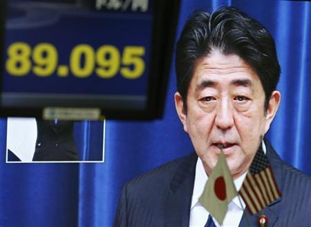 A television screen shows Japan's Prime Minister Shinzo Abe speaking at a news conference behind a monitor showing the Japanese yen's exchange rate against the U.S. dollar at a foreign exchange trading company in Tokyo January 11, 2013. REUTERS/Toru Hanai