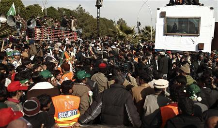 Supporters of Sufi cleric and leader of the Minhaj-ul-Quran religious organisation Muhammad Tahirul Qadri gather around Qadri 's vehicle (R) as he addresses them on the second day of protests in Islamabad January 15, 2013. REUTERS/Zohra Bensemra