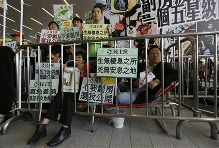Protesters sit on a make-shift bed depicting sub-divided residential units to protest against high property prices outside the Legislative Council in Hong Kong January 16, 2013. REUTERS/Tyrone Siu