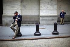 Трейдеры возле здания Нью-Йоркской фондовой биржи 27 марта 2009 года. file photo. Точно так же, как люди привыкают терпеть ноющую зубную боль, экономика США учится жизни на грани бюджетного обрыва, и текущая неделя готова представить нам свежие свидетельства этого явления. REUTERS/Eric Thayer/Files