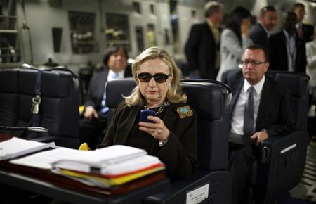 U.S. Secretary of State Hillary Clinton checks her PDA upon her departure in a military C-17 plane from Malta bound for Tripoli, Libya October 18, 2011. REUTERS/Kevin Lamarque