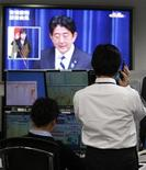 La economía de Japón se contrajo en la segunda mitad de 2012 y va camino a un flojo crecimiento de un 0,8 por ciento este año, golpeada en parta por su disputa territorial con China, dijo el martes el Banco Mundial en un informe. En la imagen del 11 de enero, unos empleados de una empresa de intercambio de divisas ven al primer ministro, Shinzo Abe, en una rueda de prensa en Tokio. REUTERS/Toru Hanai
