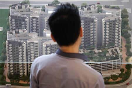 A man looks at a model of a new public housing estate to be launched at the Housing Development Board (HDB) gallery in Singapore January 15, 2013. REUTERS/Edgar Su