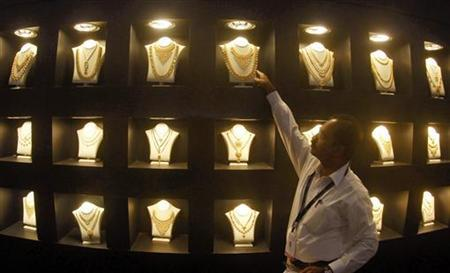 An employee displays gold necklaces at the 'Gem and Jewellery India International Exhibition 2010' (GJIIE) in Chennai January 23, 2010. REUTERS/Babu/Files