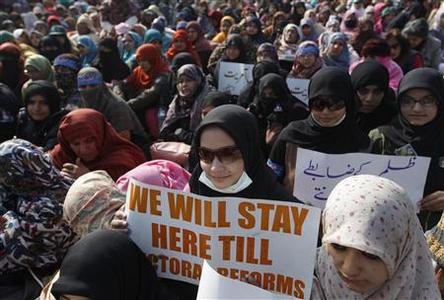 Women supporters of Sufi cleric and leader of the Minhaj-ul-Quran religious organisation Muhammad Tahirul Qadri hold placards on the third day of protests in Islamabad January 16, 2013. REUTERS/Akhtar Soomro