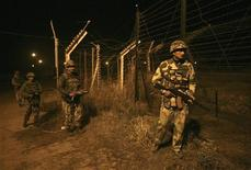 Indian Border Security Force (BSF) soldiers walk during night patrol near the fenced border with Pakistan in Abdullian, southwest of Jammu January 14, 2013. REUTERS/Mukesh Gupta