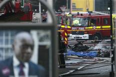 Smoke rises from debris as police and emergency services attend the scene of a helicopter crash in Vauxhall, south London January 16, 2013. A helicopter crashed into a crane near a railway station in central London during the morning rush hour on Wednesday, bursting into flames and throwing plumes of smoke into the air. REUTERS/Stefan Wermuth