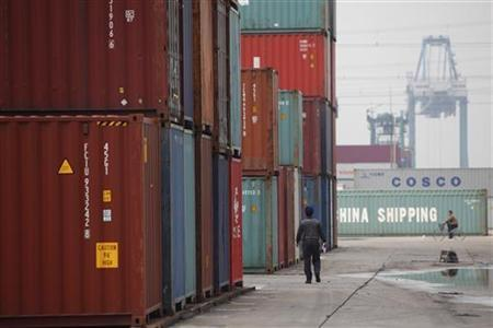 A man walks in a shipping container area at the Port of Shanghai April 10, 2012. REUTERS/Aly Song