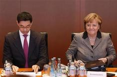 German Chancellor Angela Merkel (R) and leader of Germany's Free Democratic party (FDP) and Economy Minister Philipp Roesler arrive for the weekly cabinet meeting in Berlin January 16, 2013. REUTERS/Tobias Schwarz (GERMANY - Tags: POLITICS)