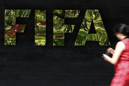 A woman walks past a logo of the International Federation of Football Association (FIFA) at the Home of FIFA in Zurich July 5, 2012. REUTERS/Michael Buholzer/Files
