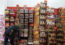 Las compras y escapadas navideñas hicieron subir el coste de vida en la zona euro en diciembre, pero el Banco Central Europeo (BCE) espera que la tasa de inflación se enfríe este año y ofrezca algún alivio a los hogares durante la recesión. En la imagen, una dependienta coloca juguetes en una tienda en Madrid el 14 de diciembre de 2012. REUTERS/Sergio Pérez