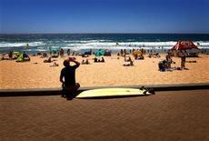 Surfista sentado a beira da praia bebe café em um dia quente de verão na praia de Manly, na Austrália. O ano de 2012 esteve entre os dez mais quentes já registrados no mundo, disseram duas agências científicas do governo norte-americano. 5/01/2013 REUTERS/David Gray