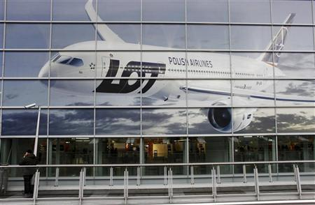 A man stands outside Chopin airport terminal near a poster of the newly purchased Boeing 787 Dreamliner by Polish airline LOT in Warsaw, December 12, 2012. REUTERS/Kacper Pempel
