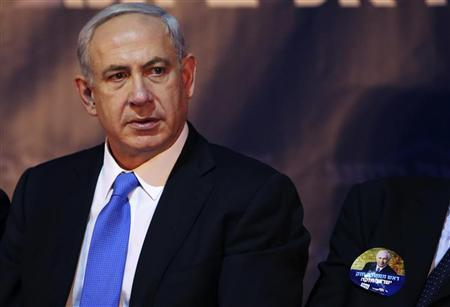 Israel's Prime Minister Benjamin Netanyahu sits next to a man wearing a sticker for Netanhyahu's campaign during a campaign conference for the coming general elections in Tel Aviv January 14, 2013. REUTERS/Nir Elias