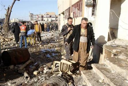 A wounded resident walks near the site of a suicide bomb blast attack in Kirkuk, 250 km (155 miles) north of Baghdad January 16, 2013. REUTERS/Ako Rasheed