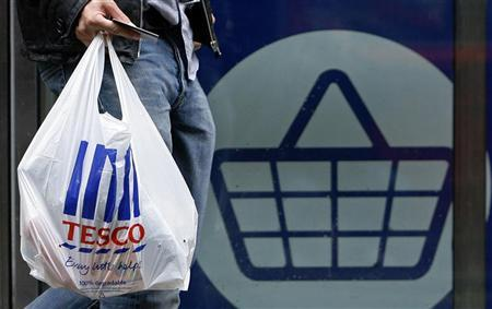 A man carries a carrier bag as he leaves a Tesco supermarket in London October 5, 2009. REUTERS/Luke MacGregor