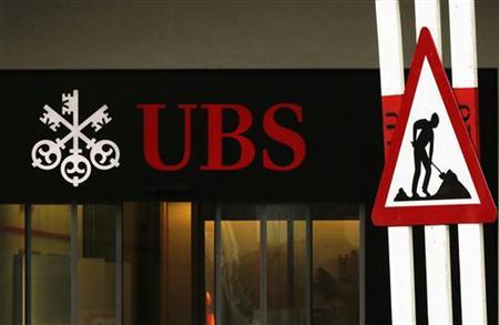 A woman woman walks past a construction road sign in front of a branch of Swiss Bank UBS in Lugano, southern Switzerland December 20, 2012. Picture taken December 20, 2012. REUTERS/Michael Buholzer