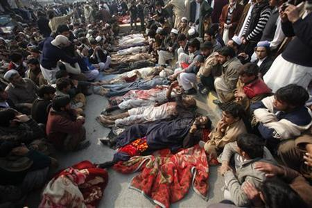 Tribesmen sit next to the bodies of their relatives, who were said to have been killed after security forces arrested them during a protest in front of government offices in northwestern Pakistan city of Peshawar January 16, 2013 REUTERS/Fayaz Aziz