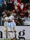 El Málaga ha cerrado un acuerdo con el Chelsea para recibir cedido al joven centrocampista brasileño Lucas Piazon, anunció el club de la Premier League. El Málaga aún tiene que confirmar oficialmente el acuerdo, pero el Chelsea indicó en su web (www.chelseafc.com) que Piazon, que cumple 19 años el domingo, se iría al club andaluz hasta final de temporada. En la imagen, varios jugadores del Málaga se abrazan durante un partido contra el Real Madrid en Málaga el 22 de diciembre de 2012. REUTERS/Marcelo del Pozo