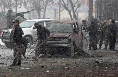 Un grupo de fuerzas de seguridad revistan el sitio de un ataque con un carro bomba en Kabul, ene 16 2013. Seis atacantes suicidas detonaron bombas en un asalto coordinado a la agencia de espionaje de Afganistán en Kabul, asesinando al menos dos personas e hiriendo a otras 22, dijeron el miércoles autoridades locales. REUTERS/Mohammad Ismail